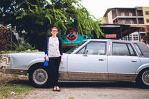 A woman standing in front of an old car.