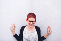 A woman with a pixie haircut touching a white wall.