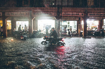 A man riding a motorcycle on a flooded street.
