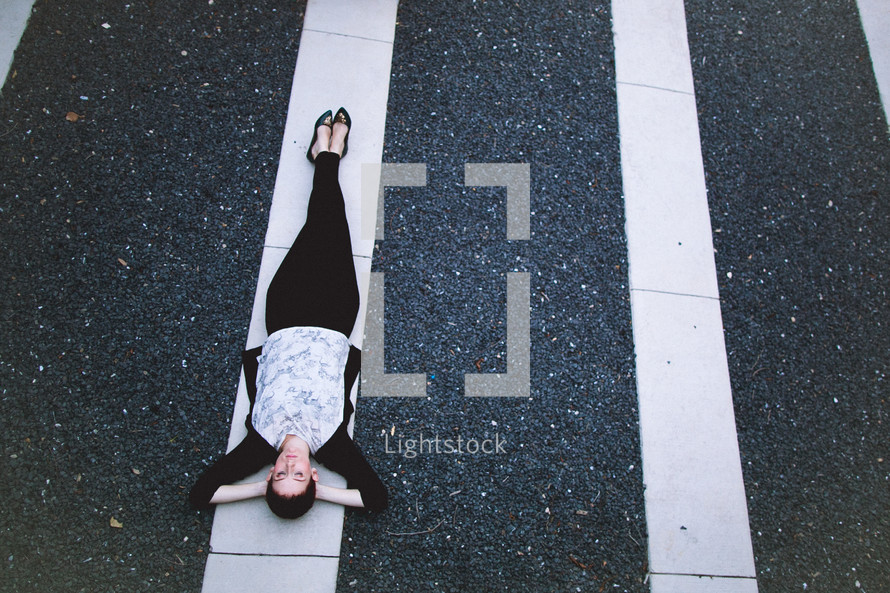 A woman lying in white lines.