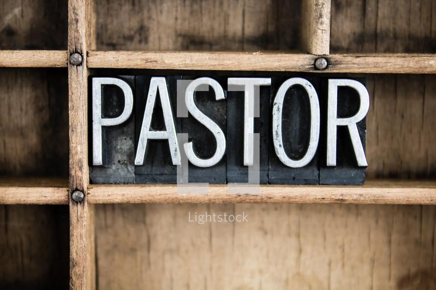 word pastor in blocks on a bookshelf