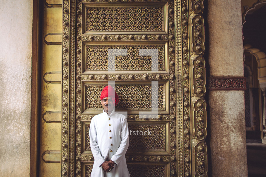 man in front of a large gold door