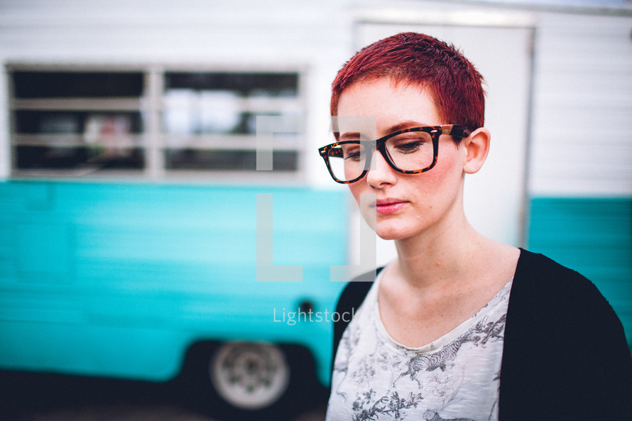 woman with short hair standing in front of an rv