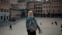 a woman walking through a courtyard carrying a map