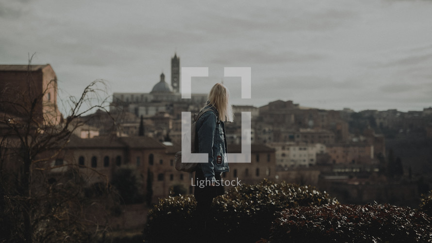 a woman with a backpack standing with an view of an ancient Eurpean City in the background
