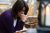 a brunette woman with head bowed in prayer