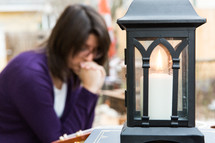 A lantern sits on a table where a woman is studying.