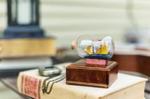 A book, pocket watch, wooden box, ship in a bottle, on a table.