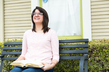 A woman looks up, smiling, while sitting on a bench with an open Bible in her lap.
