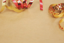 Shiny Christmas ribbon creates a border on brown paper.