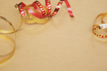 Shiny Christmas ribbon creates a border on brown paper.