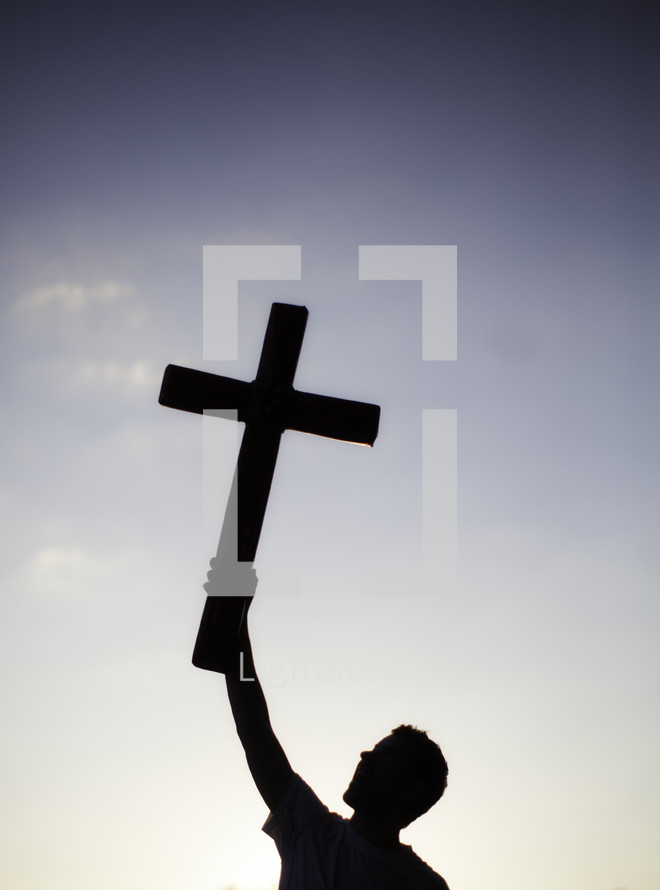 Silhouette of man holding cross with one hand in the air over his head.