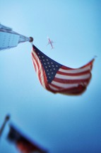 plane flying over a flag pole
