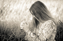 woman praying in a field