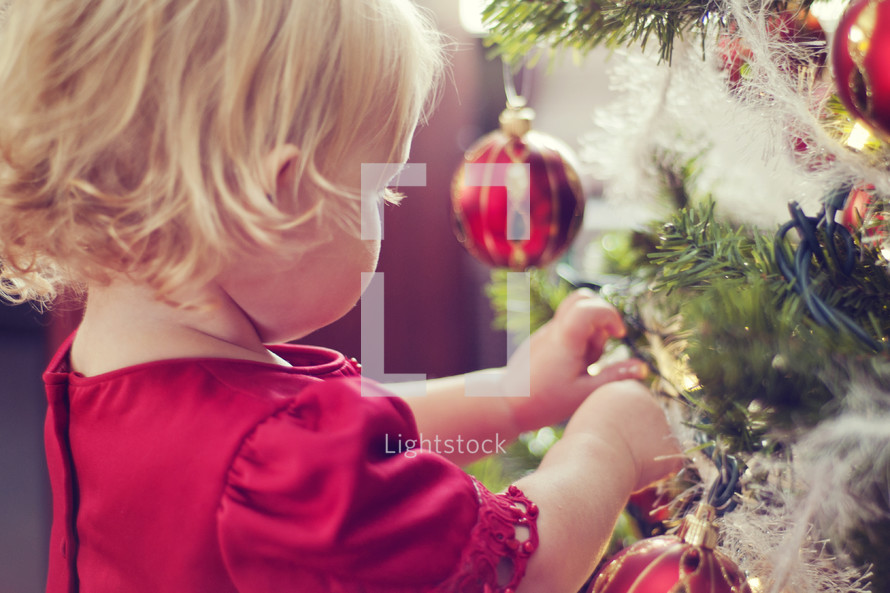 toddler hanging Christmas ornaments