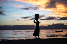 a woman standing on a beach at sunset
