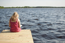 woman reading a Bible sitting on the end of a dock
