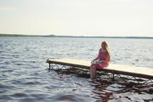 woman sitting on a dock reading a Bible