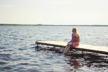 woman sitting on a pier reading a Bible