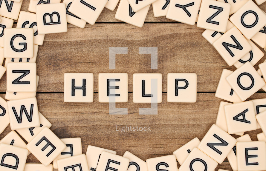 scrabble pieces and the word help