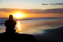 silhouette of a man sitting on a rock on a beach at sunset