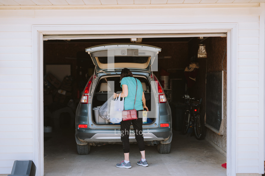 getting groceries out of the trunk of a car