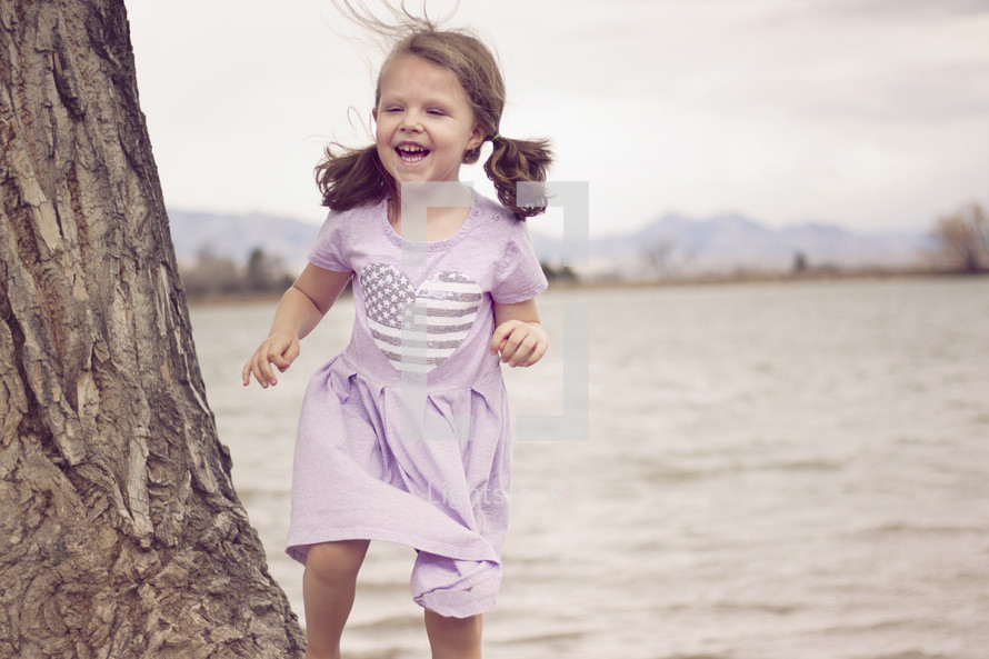a girl laughing running beside a lake shore