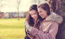 teen girls looking at a cellphone screen