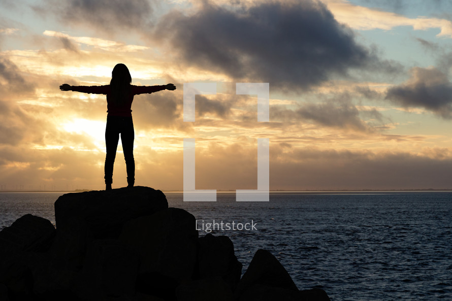 a woman standing on a rock by a shore with outstretched arms