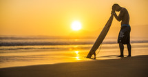 surfer in prayer over his surfboard at sunrise