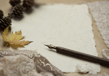 pinecones, fall leaf, pen, lace, and old paper