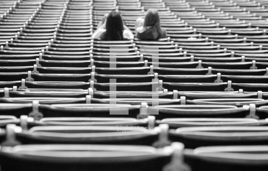 girls sitting in stadium seats