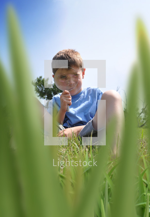 a little boy searching for bugs in the grass