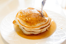 fork and plate and syrup on pancakes