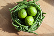 limes and green beans in a bowl