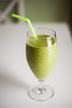 A green smoothie in a glass with a green straw.