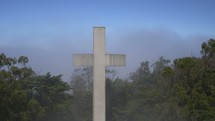 A white cross in the forest with fog