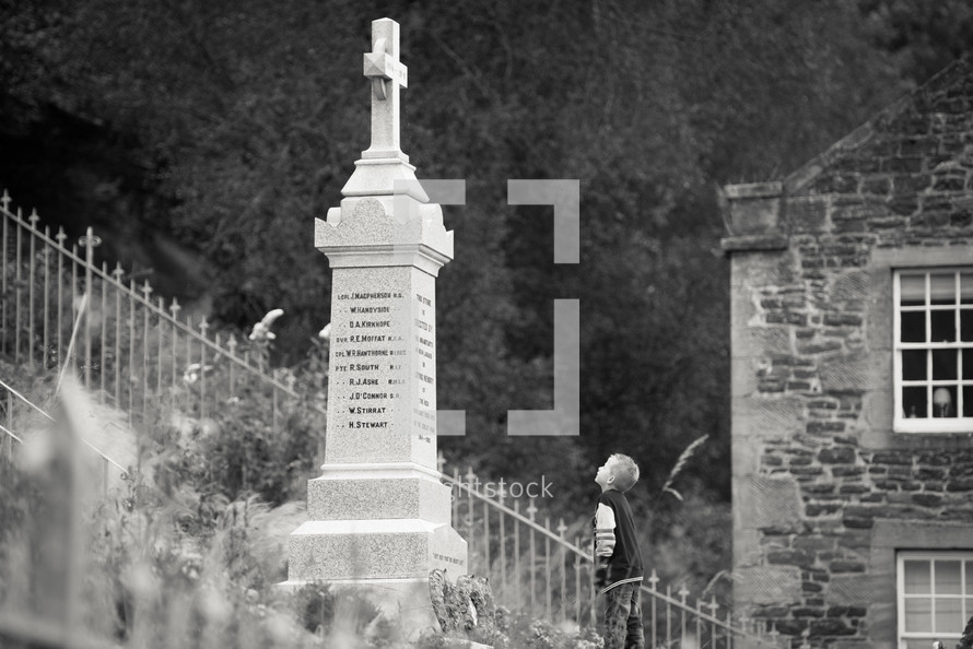 grave monument - boy looking up at it