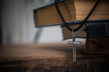 cross necklace on a stack of books and Bible