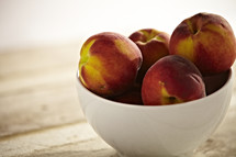 A bowl of peaches sit on a wooden table.