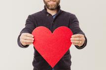 man holding a paper heart cutout