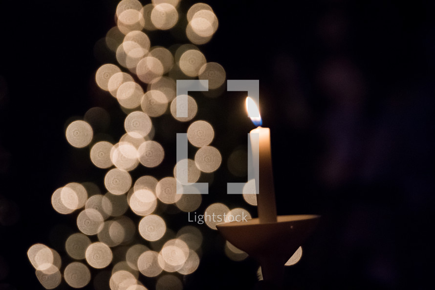 bokeh lights and candles at a Christmas Eve worship service