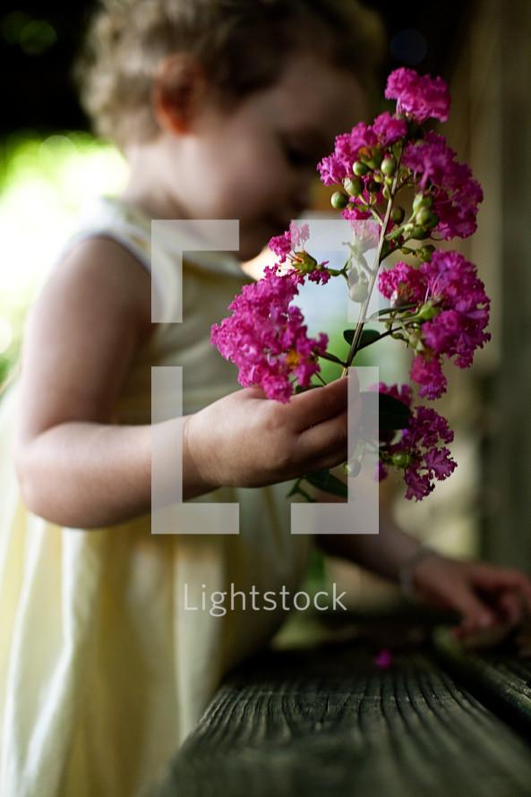 toddler girl holding branch of flowers