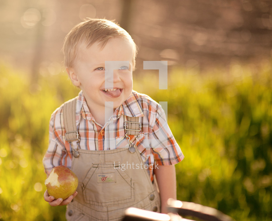Smiling boy eating an apple