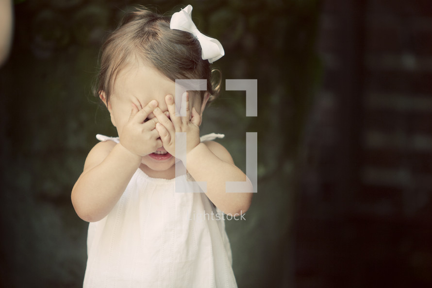 A little girl with her hands over her eyes.