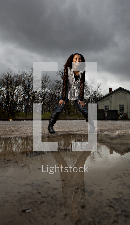 A young girl standing in front of a puddle of water