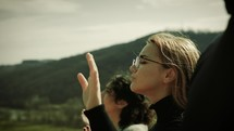 woman with hands raised in praise on a mountaintop