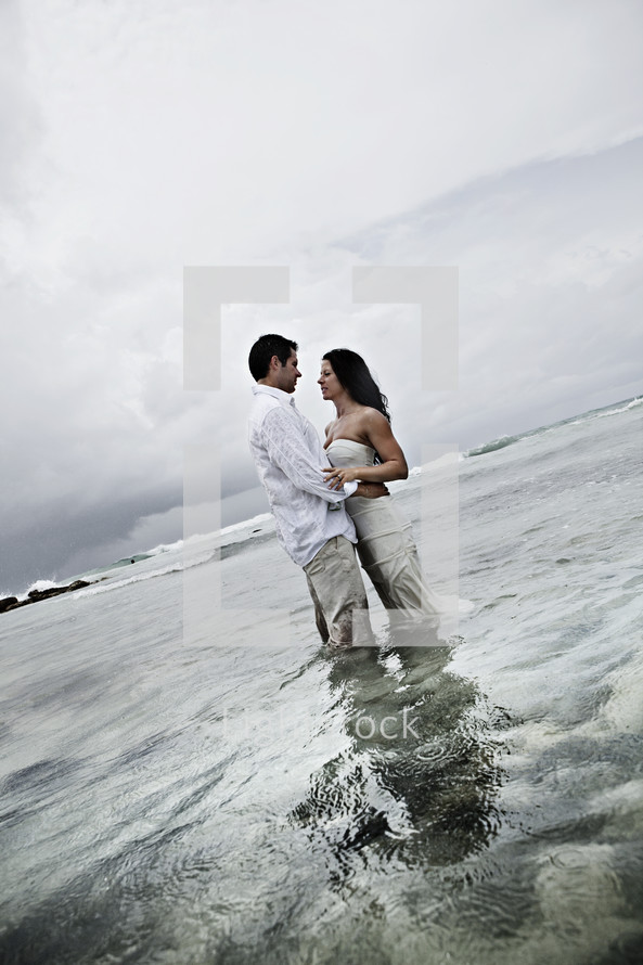 A bride and groom embracing in the water