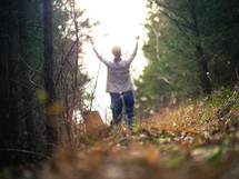 a woman standing in a forest in fall leaves with hands raised