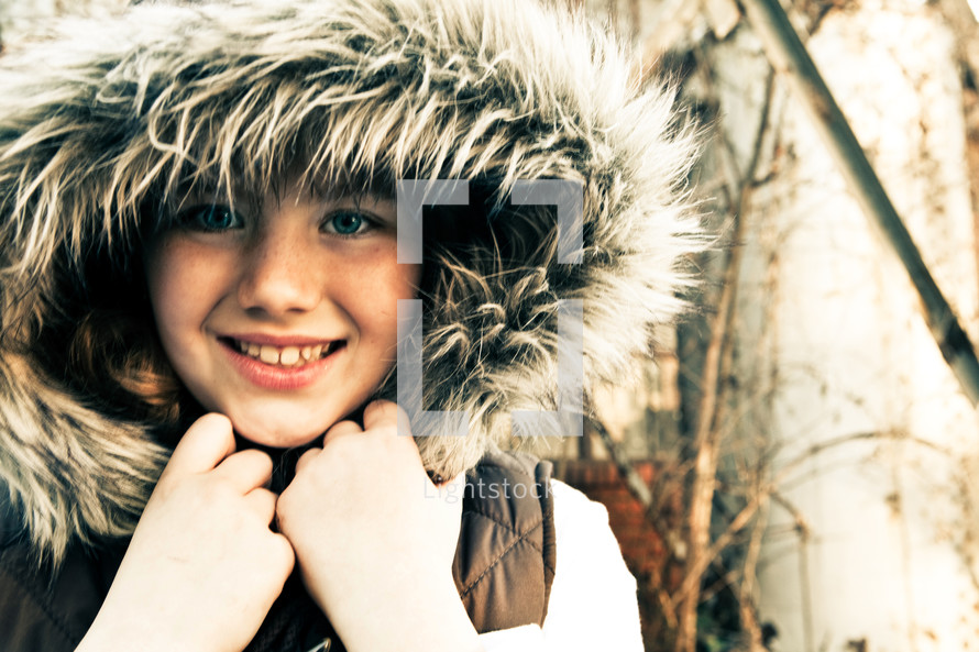 Young girl wearing a winter coat with furry hood